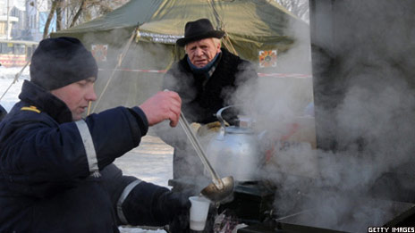 A social worker gives out tea to a man